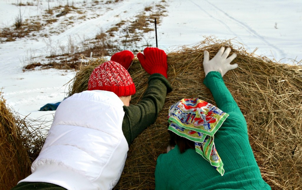 Grace and Sarah tip over a hay bale for the little people to slide down.